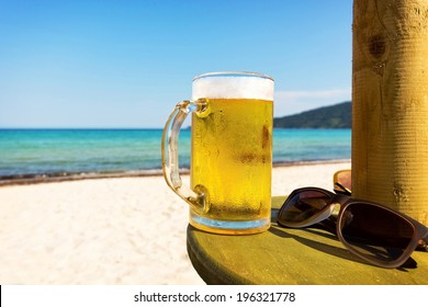 Pint of cold beer on top of the beach table.