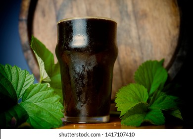 Pint dark beer nicely with a leaf of hops on the background of the barrel. Close up.