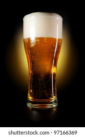 Pint glass of beer amber color with head on a black background. Isolated path included.