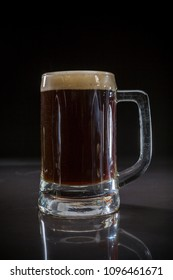 Pint glass of black beer, Glass of dark beer on black background, Beer glass with dark cold beer, Mug of frosty dark stout with bubble foam  froth