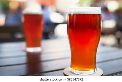 Pint glass of craft beer indian pale ale on wooden table in beer garden