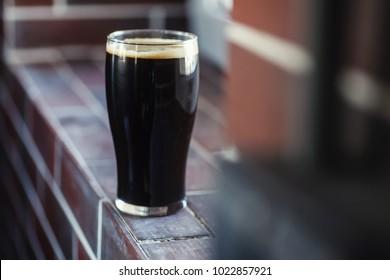 Pint glass of dark stout beer standing on a grunge brick windowsill