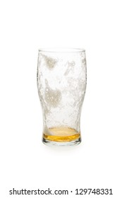 Pint glass with just a little beer in the bottom of the glass.