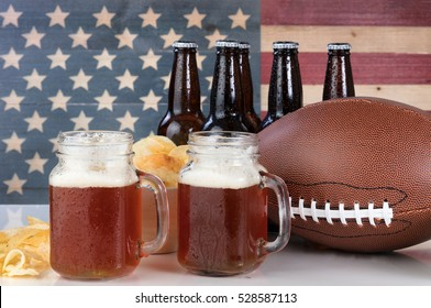 Pint glasses of beer, football, bowl of potato chips, cold beer in bottles on white glass table with United States flag painted on rustic wood. Layout in horizontal format.