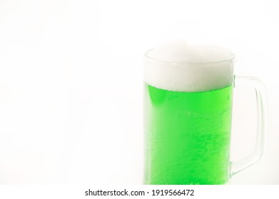 A pint of green beer for st patrick's day on a white background. Traditional Irish drink for a holiday