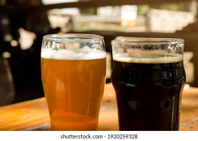 pint of lager and pint of stout. Craft beer in beer garden with wooden table