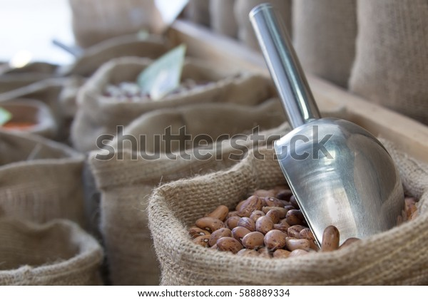 Pinto beans in a bag of hemp arranged to stand in a store.
