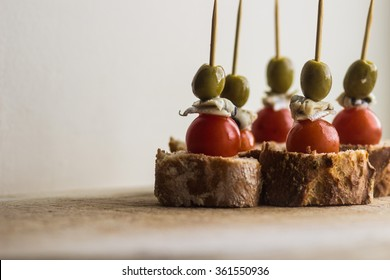 """""""Pintxos"""" Basque Tapa Set on a Rustic Board, food from the Basque Country. olive, anchovy, cherry tomato and bread"""