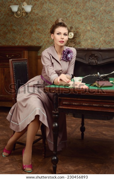 Pinup beautiful young woman 50s American style in vintage interior drinking tea