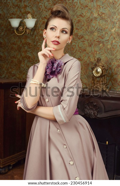 Pinup beautiful young woman 50s American style stay in vintage interior by the fireplace