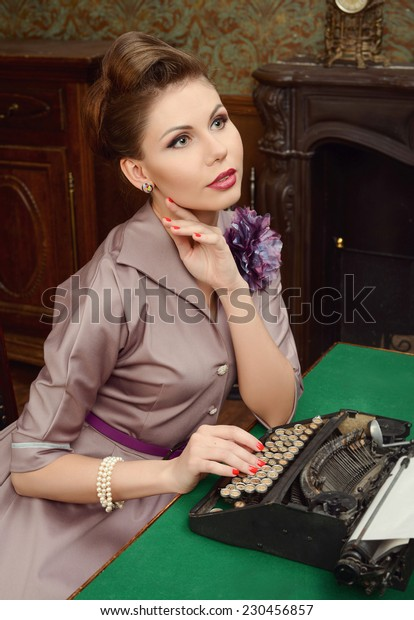 Pinup beautiful young woman in vintage interior prints on an old typewriter