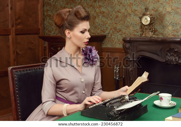 Pinup beautiful young woman in vintage interior reading a book and prints on an old typewriter