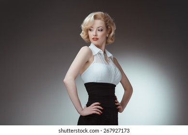 Pin-up girl, 50 style. Studio shot of young and beautiful woman wearing white blouse and black fitting, in studio. Professional makeup and hair style