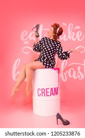 pin-up girl in black polka dot dress on pink background on iron barrel