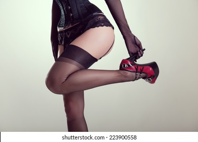 Pinup girl in corset and vintage nylon stockings holding high heel shoe, studio shot with vintage tone