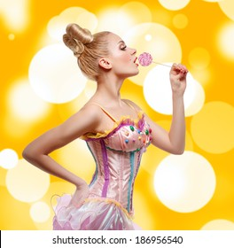 Pin-Up Girl dressed as a doll with lollipop. Bright yellow background.