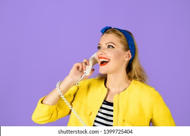 Pinup girl with handset. Smiling woman dressed in yellow jacket holds telephone handset. Happy woman holds handset. Pretty woman talking at retro handset. Girl talking on landline phone. Communication