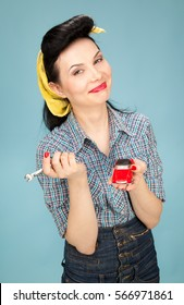 Pin-up girl with a red toy car and a spanner