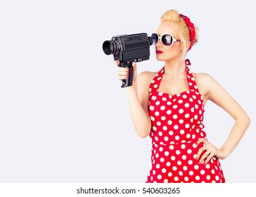 Pin-up girl with red vintage dress  holding vintage 8 mm camera