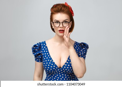 Pin-up style portrait of beautiful young redhaired woman in vintage dress with low cut neck posing in studio, holding hands at her mouth, sharing secret, gossip or rumour with you, having excited look