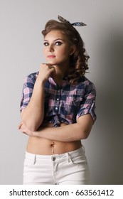 Pinup woman in checkered shirt and with piercing poses in grey studio