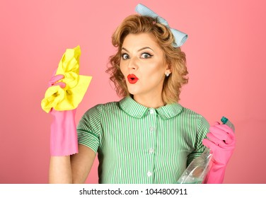 Pinup woman hold soup bottle, duster. Housekeeper in uniform with clean spray, duster. Cleaning, retro style, purity. Cleanup, cleaning services, wife, gender. Retro woman cleaner on pink background.