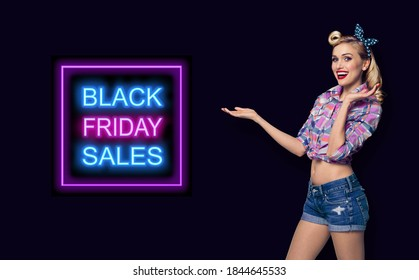 Pinup woman holding, pointing or giving something. Excited girl in pin up cloth, showing some product or copy space for slogan or text. Retro and vintage concept. Dark background. Black Friday sales.