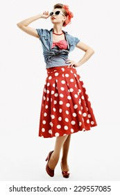 Pinup young woman in vintage American style isolated on white studio background, dressed in a red dress with polka dots and denim vest