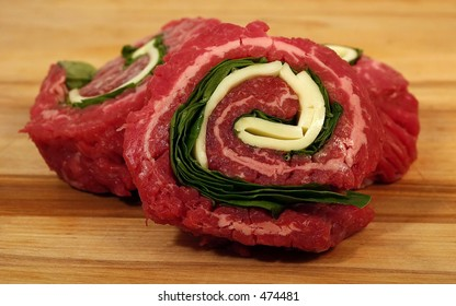 Pinwheel steaks on a cutting board.