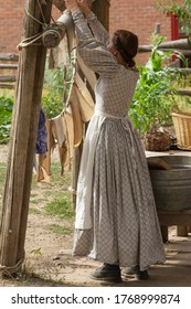 Pioneer woman hanging clothes outside