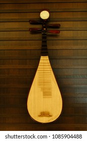 A pipa hanging on a wall. It is a four-stringed Chinese musical instrument.