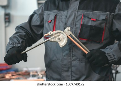 Pipe bender tool in a hands of factory worker on a factory workbench background. Fitter is bending a pipe. Pipework.