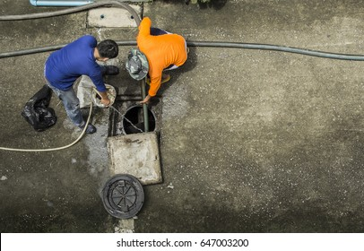Pipe cleaning drainpipe by two workers to get rid of obstruction Passage of water in the rainy season in image bird eye view.