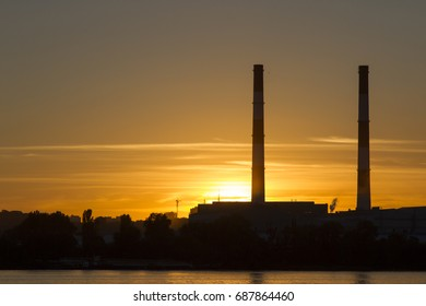 Pipe factory against the background of the river sunset