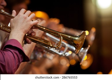 The pipe is in the hands of a musician in the orchestra