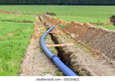 Pipe laying construction site on a meadow.
