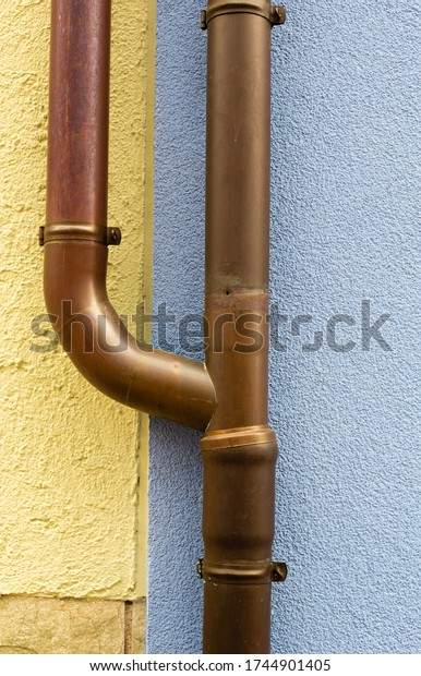 Pipe on the building facade. Rainwater drainage. House drainage system. Metal pipe. New facade The building has been renovated.