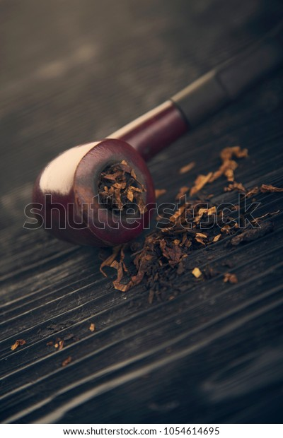 pipe smoking tobacco on a wooden black bg close up