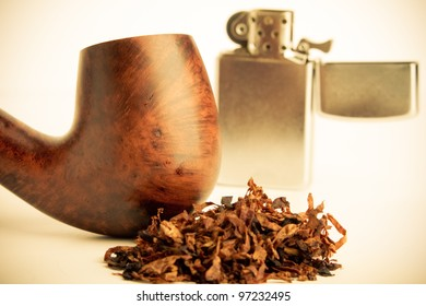 Pipe - This is a shot of an old pipe with a pile of tobacco sitting in front with an out of focus lighter in the background. Shot in a warm retro color tone at a shallow depth of field.