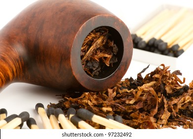 Pipe Tobacco - This is a photo of an old pipe filled and spilling with tobacco with a bunch of matches laying around. Shot with a shallow depth of field.