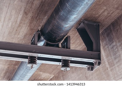Pipe under a concrete bridge with dampers and steel support to keep it steady