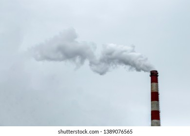 The pipe from which the smoke goes against the gray sky. The concept of air pollution, CO2, carbon dioxide gas, exhaust gases.