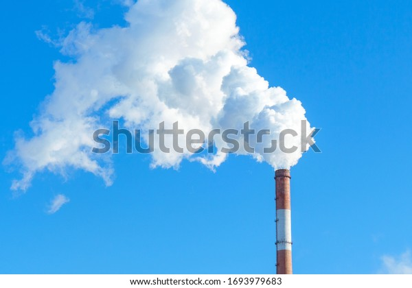 Pipe with white smoke against the background of blue sky and copy space. emission of steam and smoke into the atmosphere