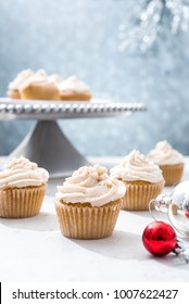 Piped eggnog vanilla holiday cupcake with a silver cake tray and additional cupcakes in the silvery background with a red ornament in the foreground.