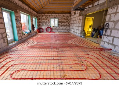 Pipefitter installing system of heating or underfloor heating installation. Water floor heating system interior. Plumbing pipes in apartment during under renovation, remodeling and construction.