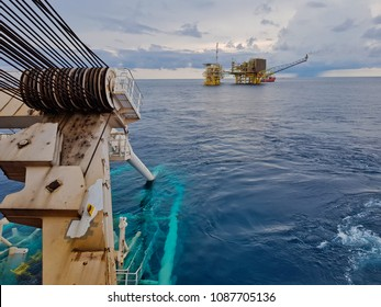 Pipelaying vessel with a pipeline stinger in the water during subsea pipeline construction/installation with an oil and gas platform in the vicinity - South China Sea, Malaysia