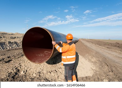 Pipeline workers measuring tube length for construction of gas and oil pipes. Energy pipe construction site.