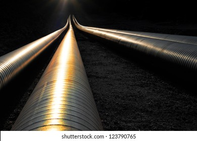 Pipelines reflecting the evening light, disappearing into darkness