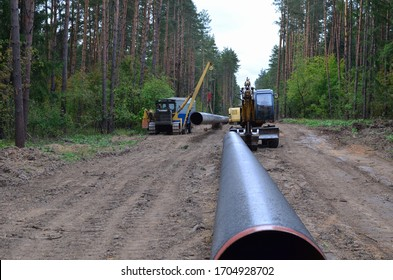 Сonstructing pipelines that transport oil, gas, petroleum products and industrial gases. Dug trench in the ground for installation of industrial gas pipes. Crawler crane with side boom or pipelayer