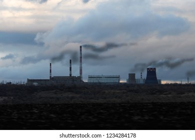 the pipes of the factory smoke against the sky